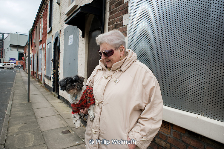A woman with her dog in Venmore Street, which leads to the Kop end of  Liverpool football stadium in Anfield.  The street is scheduled for demolition by the Merseyside NewHeartlands partnership, financed by the Housing Market Renewal Fund, part of a government strategy aimed at tackling 'low demand'.  Some long-standing residents oppose the demolition of their homes.