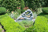 Boxwood Buxus surrounding mother and child garden sculpture statue, with yarrow Achillea, Acorus, hedges