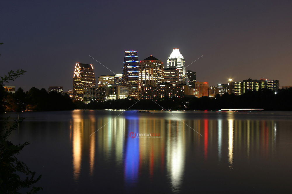 Austin, Texas downtown night city skyline with lights reflecting on the calm water of Townlake in Austin, Texas.