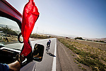 SULAIMANIYAH, IRAQ: A referee in an escort vehicle waves a red flag to alert another on the road that cyclist Nyan Yassin is approaching during an event.<br /> <br /> Nyan Yassin, 24, is a professional competitive cyclist in Sulaimaniyah in the semi-autonomous region of Iraqi Kurdistan.  She is the captain of an all-female club called Newroz Club, which is the only cycling club for women in Sulaimaniyah, although there are other clubs around Iraq.  She trains and competes on roads that are badly surfaced and busy with traffic.<br /> <br /> Nyan was the first woman to start cycling in Sulaimaniyah.  She was always competitive and after trying her hand at different sports she settled on cycling.  She is now the top female cyclist in Iraq.  Her nickname is MigMig after the noise made by the cartoon character Roadrunner.<br /> <br /> Despite being clearly talented at her sport Nyan knows that in a couple of years she will have to get married and then abandon it as, in the traditional society that Kurdistan is, being a wife and a competitive sportswoman at the same time is not an option.<br /> <br /> Photo by Gona Hassan/Metrography