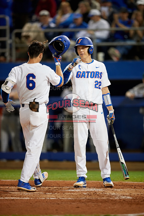 Florida Gators JJ Schwarz (22) greets Jonathan India (6) after hitting a solo home run during a game against the Siena Saints on February 16, 2018 at Alfred A. McKethan Stadium in Gainesville, Florida.  Florida defeated Siena 7-1.  (Mike Janes/Four Seam Images)