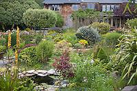 Artist's backyard cottage garden with pond. House in background. Sally Robertson Garden.