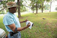 Henry Childress of Fayetteville uses a guide to locate graves Tuesday July 20, 2021at Oaks Cemetery which is located just south of the National Cemetery in Fayetteville. Many of the black citizens who lived and died in Fayetteville in the decades after the Civil War are buried in Oaks Cemetery. The Oaks Cemetery Group was formed in 2009 to reclaim the cemetery from the weeds and grass. Established in 1867, the cemetery is on the Arkansas Register of Historic Places. Visit nwaonline.com/21000721Daily/ and nwadg.com/photo. (NWA Democrat-Gazette/J.T. Wampler)