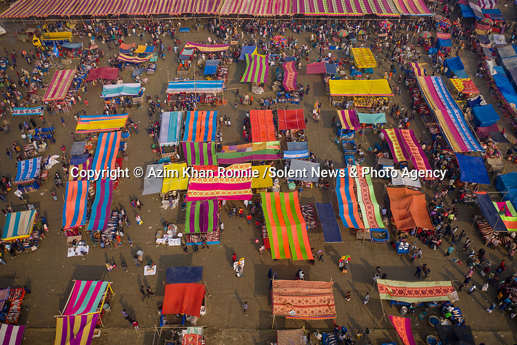 "The colourful canopies of market stalls at a centuries old fish festival resemble beach towels from above in this vibrant scene from Bogura, Bangladesh.<br /> <br /> The drone shots were captured by Azim Khan Ronnie,  34, a freelance photographer from Dhaka.<br /> <br /> Azim said, ""this ancient fish fair, on the banks of the Ichhamati River, has been held for more than 400 years.  It is only held for one day, and people travel from all over the country to experience it.""<br /> <br /> ""One of the main attractions is the sheer variety of fish on offer.  It also serves as a meeting place for all religions, tribes and faiths.  The economic importance can't be underestimated either; the lower classes benefit greatly from the sales they make.""<br /> <br /> Please byline: Azim Khan Ronnie /Solent News<br /> <br /> © Azim Khan Ronnie /Solent News & Photo Agency<br /> UK +44 (0) 2380 458800"