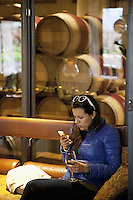 USA. California state. Napa valley. Barrels of wine in the cellar of Robert Mondavi Winery, To Kalon Vineyard. A tourist woman seats on a couch, reads messages on her cellular phone and enjoys a glass of red wine. Robert Gerald Mondavi (June 18, 1913 – May 16, 2008) was a leading California vineyard operator whose technical improvements and marketing strategies brought worldwide recognition for the wines of the Napa Valley in California. 16.12.2014 © 2014 Didier Ruef