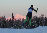 Morning light illuminates Denali as Elizabeth Guiney of Craftsbury GRP competes in the Women's 20k Classic during the 2018 U.S. National Cross Country Ski Championships at Kincaid Park in Anchorage.