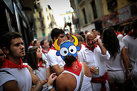 Participants is seen during the San Fermin Festival, on July 7, 2012, in Pamplona, northern Spain. The festival is a symbol of Spanish culture that attracts thousands of tourists to watch the bull runs despite heavy condemnation from animal rights groups . (c) Pedro ARMESTRE