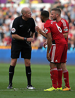Referee Lee Mason speaks to Adrian Mariappa of Watford and his team mate during the Premier League match between Swansea City and Watford at The Liberty Stadium, Swansea, Wales, UK. Saturday 23 September 2017