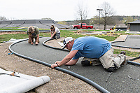 Steve Kerstiens, (from foreground) Terry Wallace and Destiny Wallace with Wallace Flooring work to trim and apply new artificial turf on one of the holes at the mini golf course at Kingsdale Play Ground in Bella Vista behind Riordan Hall. <br /> (NWA Democrat-Gazette/Spencer Tirey)
