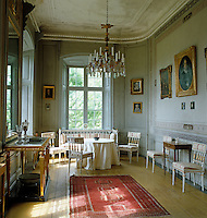The walls of the Countess's Cabinet are decorated with hand-painted borders and the room is furnished with a suite of white-painted late Gustavian chairs