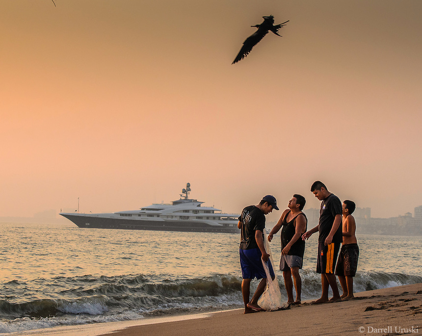 Fine Art Print Photograph of the Attessa IV Yacht and a Magnificent FrigateBird flying over a group of net fishermen in Puerto Vallarta, Mexico.