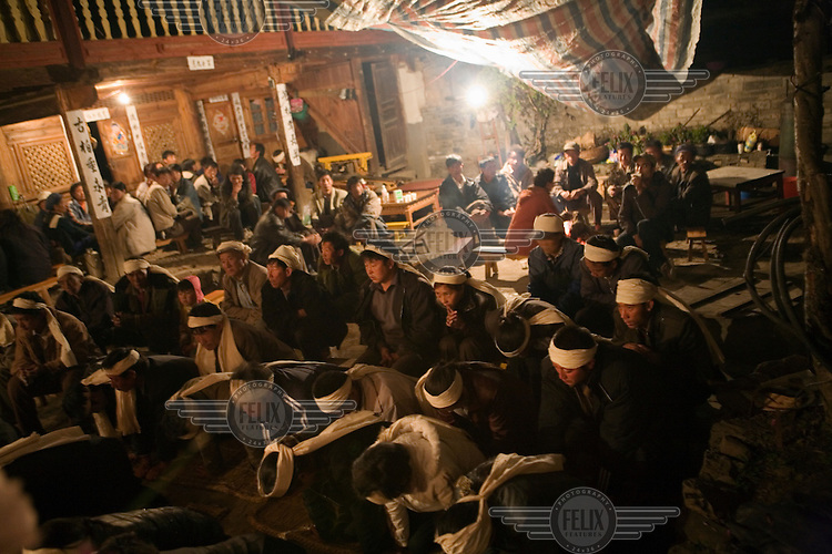 Funeral preparations in the traditional Nakhi (Naxi) town of Lu Dian on the outskirts of Lijiang county. The family, a mix of Naxi and Han Chinese, has had a family member pass away, and are wearing white head bands to signify this loss.