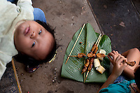 A Kichwa (Quechua) baby lies on the floor in the Sunday Market, next to a child eating roasted Mayon grubs.