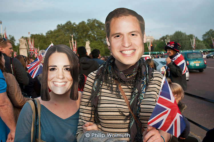 Spectators with face masks outside Buckingham Palace on the eve of the Royal Wedding.