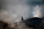 A young girl makes her way through poisonous gases and fumes originating from the burning coal beneath the surface. These places are so hot and suffocating people who are not used to such exposure will fall sick. A huge coal mine fire is engulfing the city of Jharia from all its sides. All scientific efforts have gone in vain to stop this raging fire. This fire is affecting lives of people living in and around Jharia. Jharkhand, India. Arindam Mukherjee.