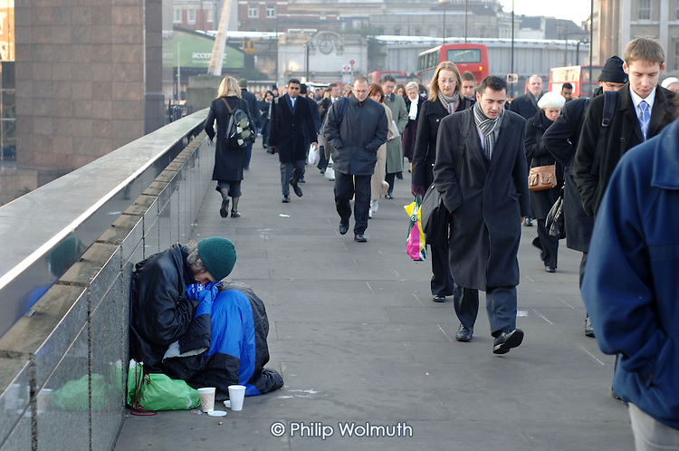 Commuters on London Bridge pass a homeless man on their way to work.