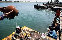 INDIA, Madhya Pradesh, Hoshangabad, Narmada river, bathing ghats an important place for the Narmada Parikrama, a holy pilgrimage along the river, woman waters a shiv lingam / INDIEN, Narmada Fluss, Hoshangabad, Hindu Pilger an Badestufen in Hoshangabad, Frau begießt einen Shiva Lingam