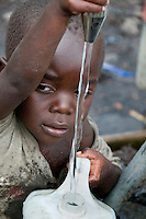 Four year old Muhindo collects water for his family in the Kibati IDP (Internally Displaced Persons) camp.