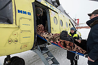 Paramedics and slight staff carry a patient onto a waiting helicopter which will fly him to the district hospital.<br /> Vladimir (name changed) (67) had a stroke in the night but due to bad weather conditions a helicopter could only fly at 10.00 am.