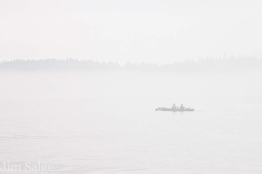 On a misty morning, two rowers work their way between islands on the New England Coast in Maine.