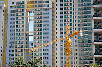 Construction crane in front of the facade of a large apartment building, Shenzhen, Guangdong, China.