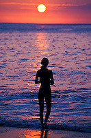 Woman standing in meditation at the shoreline of the ocean during sunset