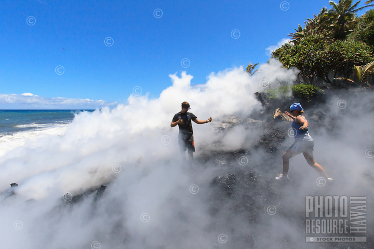 A couple, surrounded by mist, gets closer to where the lava meets the ocean at Fox's Landing black sand beach on the Big Island.