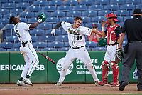 Tulane Green Wave Walker Burchfield (39) pumps his fist after hitting a home run during a game against the Houston Cougars on May 25, 2021 at BayCare Ballpark in Clearwater, Florida.  Tulane defeated Houston 4-1 in the opening game of the American Athletic Conference Tournament.  Jared Hart (8) and catcher Dylan Post (31) look on.  (Mike Janes/Four Seam Images)
