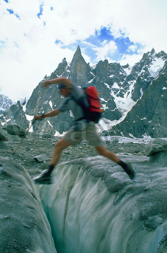 Blurred climber leaping from one rock to another with the Hidden Spires of Karakoram, Pakistan in the distance.