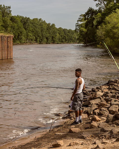 May 4, 2018. Fayetteville, North Carolina.<br /> <br /> D'Anthony Brown fishes at the William O Huske Dam. This is the dam closest to the Chemours plant.<br /> <br /> The Chemours Company, a spin off from DuPont, manufactures many chemicals at its plant in Fayetteville, NC. One of these, commonly referred to as GenX, is part of the process of teflon manufacturing. Chemours has been accused of dumping large quantities of GenX into the Cape Fear River and polluting the water supply of city's down river and allowing GenX to leak into local aquifers.