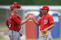 GCL Nationals relief pitcher Gilberto Chu (61) high fives catcher Alex Dunlap (27) after completing the second game of a doubleheader against the GCL Marlins on July 23, 2017 at Roger Dean Stadium Complex in Jupiter, Florida. GCL Nationals defeated the GCL Marlins 1-0 as Johnson combined with starting pitcher Jared Johnson (not pictured) to throw a seven inning no-hitter. (Mike Janes/Four Seam Images)
