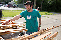 """Joseph Zongolowicz unloads wood from a truck as he and other members move it into a dumpster during """"Circle the City with Service,"""" the Kiwanis Circle K International's 2015 Large Scale Service Project, on Wednesday, June 24, 2015, at the Friendship Westside Center for Excellence in Indianapolis. (Photo by James Brosher)"""