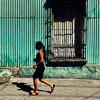 A Salvadoran girl walks in front of a common lower middle class house, designed by using bold Spanish colonial architecture elements, built in a working class neighborhood of San Salvador, El Salvador, 15 November 2016.
