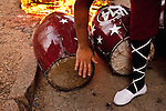 A drummer tests a drum as it heats by a fire prior to the parade of Llamadas during Carnaval in Montevideo, Uruguay.