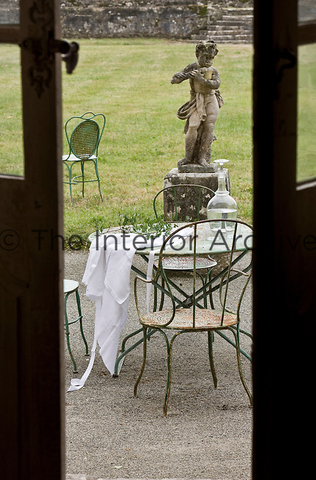 In the garden a stone statue of Pan watches over a metal garden table and chairs beyond the double windows