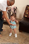 13 month old baby girl at home walking to father who is her primary caregiver first steps vertical