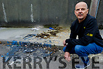 Cllr Tom Barry of the Listowel Municipal District on Tuesday kneeling by the rubbish dumped in a laneway in Listowel.