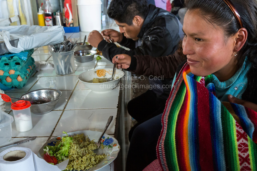 Peru, Cusco, San Pedro Market.  Woman Having Lunch at a Food Counter in the Food Court Area of the Market.