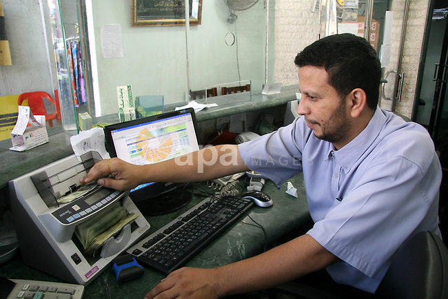 """Palestinian man exchanges currencies in Gaza City. the U.S. dollar fall versus the shekel rise in black markets in the Gaza Strip, Hamas spokesman Fawzi Barhum said in a statement that the Financial crisis U.S.was due to """"bad administrative and financial management and a bad banking system put into place and controlled by the Jewish lobby."""