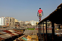 A man walks above huts in the Mirpur slum in Dhaka.