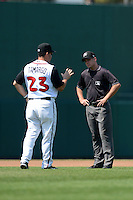 Lansing Lugnuts manager John Tamargo (23) argues a call with umpire Jimmy Lott during a game against the Dayton Dragons on August 25, 2013 at Cooley Law School Stadium in Lansing, Michigan.  Dayton defeated Lansing 5-4 in 11 innings.  (Mike Janes/Four Seam Images)