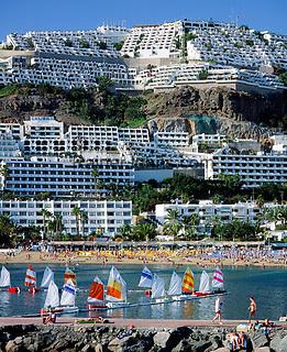 Spanien, Kanarische Inseln, Gran Canaria, Puerto Rico: Strand, Mole, Optimisten, Segelboote   Spain, Canary Island, Gran Canaria, Puerto Rico: beach, sailing boats