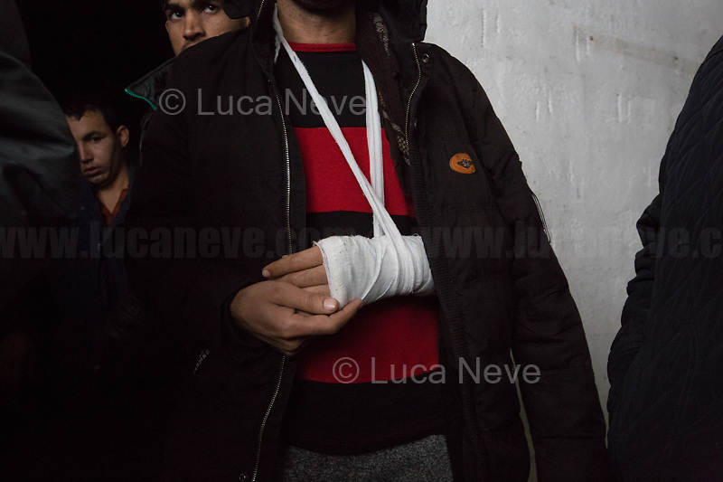 """Ihsanullah from Afghanistan: left arm broken and beaten on the left shoulder with a police truncheon. Phone, money, clothes, shoes took away allegedly by the Croatian border police.<br /> <br /> Bihać, Bosanska Krajina, Bosnia, 15/12/2018.The Bira camp is a former fridge factory located outside Bihac. It is managed by the UN (ONU) agency called IOM (OIM) - International Organization for Migration. The camp is a huge hangar and it composed by tents and containers (mainly located in the area dedicated to most vulnerable people and families) 'donated' by the EU, Turkkizilayi, Crveni Kriz Grada Bihaca. The camp has got also a Health clinic, the """"Klinika"""", provided by DRC Danish Refugee Council and UNHCR and EU (UE). The People met outside the Klinica who showed their medical refers, their wounds and injuries claimed that they were beaten up by the Croatian Police which also allegedly stole their money and broke their smartphones after they were found trying to cross the border between Bosnia & Croatia, the beginning of the so called """"The Game"""" (1). The very dangerous end of the """"Balkan route"""", the undetected border crossing throughout Croatia and then Slovenia, which people try numerous times to reach Italy or Austria. If they caught crossing any of the borders, they will be deported back to Bosnia, at """"square 1 of the Game"""".<br /> Clothes, food and a little bit of entertainment for the Children are provided by the Crveni Kriz Grada Bihaca, the Bosnian Red Cross, which also manages a sort of canteen.<br /> The IOM (OIM) provided data about the People living in the Bira camp while this reportage was made:<br /> -2067 people are the inhabitant of the camp (but obviously the number changes a lot and often)<br /> -187 unaccompanied minors all boys, mostly from Pakistan;<br /> -80 families: 325 family members, 145 children, 78 boys, 67 Girls.<br /> <br /> 1. http://bit.do/fgwYL"""