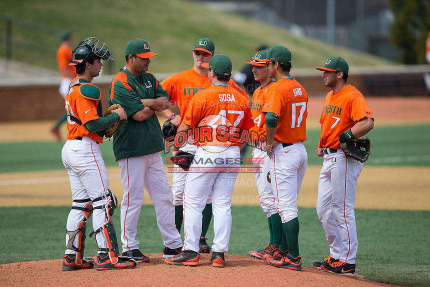 Miami Hurricanes pitching coach J.D. Arteaga (green jacket) has a meeting on the mound with starting pitcher Enrique Sosa (47), catcher Garrett Kennedy (40) and the entire infield during the game against the Wake Forest Demon Deacons at Wake Forest Baseball Park on March 22, 2015 in Winston-Salem, North Carolina.  The Demon Deacons defeated the Hurricanes 10-4.  (Brian Westerholt/Four Seam Images)