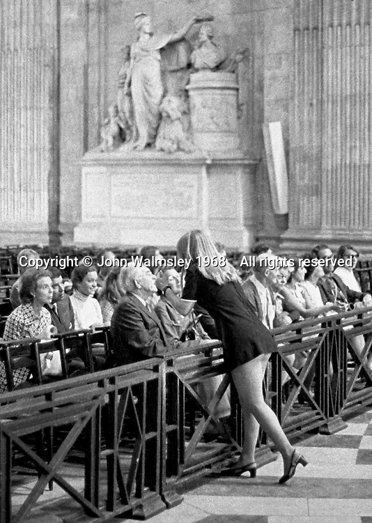 A tour guide inside St Paul's Cathedral, London, wearing a miniskirt.  1968.