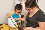 3 year old boy at home cooking baking activity with mother pouring batter into pan, mother assisting by holding bowl