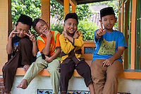 "Borobudur, Java, Indonesia.  Indonesian Gestures.  Young Boys waiting for Friday Noon Prayers at Neighborhood Mosque.  The V is a common gesture (boy on left) in Indonesia when the person being photographed wants the photo to be a good one.  Holding the thumb up with the index finger extended straight is an Indonesian gesture meaning ""looking good.""  (second from left) Crossing the wrists near the face means ""keep smiling."" (third from left)"
