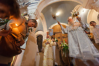 """Switzerland. Geneva. Easter at the Russian Church. The church is a lovely 19th-century Russian Orthodox church and designed in a Byzantine Moscovite style. The church's full name is Cathédrale de l'Exaltation de la Sainte Croix. After midnight on the night of Easter Sunday, the Archbishop Michael, priests, deacons and congregation go in a procession around the church, holding lit candles, chanting: By Thy Resurrection O Christ our savior, the angels in Heaven sing, enable us who are on Earth, to glorify thee in purity of heart. This procession reenacts the journey of the Myrrhbearers to the Tomb of Jesus """"very early in the morning"""". After circling around the church once, the procession halts in front of the  church's closed doors which represent the sealed tomb. Then, the Archbishop Michael makes the sign of the cross with the censer in front of the closed doors and blesses a crowd of believers. He holds in his left hand the Paschal Trikirion which is a liturgical triple-candlestick used at Easter time in the Eastern Orthodox ceremony. It is used from the commencement of the celebration of the Resurrection during the Paschal Vigil. The nighttime liturgy is a blessing of Easter fire with candles and the celebration of the Easter Proclamation of the Resurrection of Jesus Christ. A priest holds in his hands the Paschal Trikirion which is a liturgical triple-candlestick used at Easter time in the Eastern Orthodox ceremony. It is used from the commencement of the celebration of the Resurrection during the Paschal Vigil. Archbishop Michael (Secular name - Simeon Vasilyevich Donskoff; born on 29 March 1943) is a bishop of the Russian Orthodox Church Outside of Russia, Archbishop of Geneva and Western Europe. Easter, also called Pascha or Resurrection Sunday is a festival and holiday celebrating the resurrection of Jesus from the dead, described in the New Testament as having occurred on the third day of his burial after his crucifixion.The Russian church serves not only"""