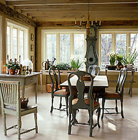 The dining area in the kitchen has a wooden trestle table and Swedish grandfather clock and is full of spring flowering bulbs