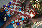 Anti-poaching commander playing checkers with Panthera cook, Kafue National Park, Zambia